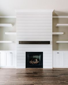 Modern rustic white shiplap fireplace featuring dark stained floating mantle, dark hardwood flooring, custom shaker cabinetry, and floating contemporary shelves Fireplace Feature Wall, Basement Fireplace, Fireplace Shelves, Fireplace Built Ins, Shiplap Fireplace, Farmhouse Fireplace, Home Fireplace, Fireplace Remodel, Modern Fireplace