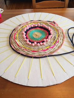 Cardboard and yarn form the simple base of this weaving loom for making a round rug! What a great idea. I can see this as a fantastic collaborative arts project using a range of different textiles that the kids bring into school! It would be amazing on display too.
