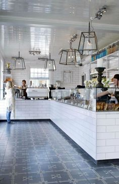 United Bakeries dark floor, dark kick board, white tiles, glass, metal pendants