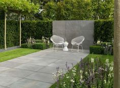 Stilvoller Garten mit Terrasse und Gartenmauer in Granit verkleidet