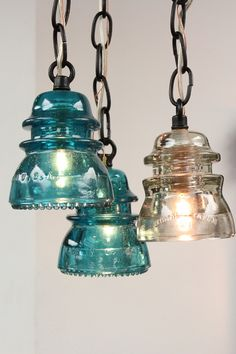 Pendant lights made from recycled chains and antique electrical glass insulator caps