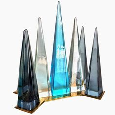 Exceptional centerpiece composed by a brass base surmounted by seven blown glass obelisks in different size and color. Made in Italy by Seguso Murano in 1960. Dim: H: 17.72 in. (45 cm), W: 11.81 in. (30 cm), D: 7.87 in. (20 cm).