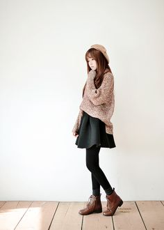 Cute winter outfit with the large oversized sweater, black skirt, black tights, brown lace up combat boots, and a beanie to top it all off.