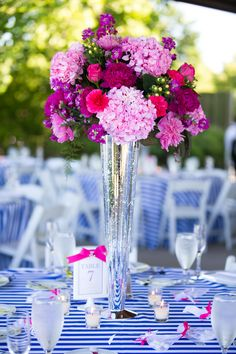 Amazing hot pink wedding flower centerpiece at this pink and blue nautical wedding reception! | Photograph by Carly Fuller Photography
