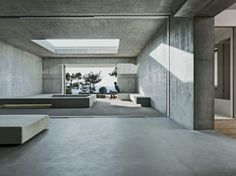 2 Verandas  Gus Wüstemann Architects  Zurich  A cutout in the terrace brings daylight to an open-air room on the ground floor. This space connects to the main living area by a sliding glass wall and features concrete benches and a square void for plants.