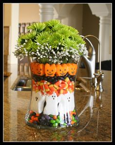 Halloween arrangement using fresh flowers and assorted halloween themed candy. (inspiration).