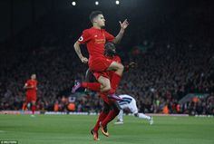 The Brazilian playmaker leaps in the air to celebrate handing Liverpool a 2-0 lead before half time