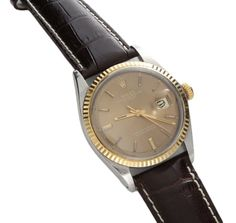 Vintage stainless steel and yellow gold gents Rolex Oyster Perpetual Datejust wristwatch, ref #1601. Brown Rolex dial with yellow gold hour markers and date wheel at 3 o`clock. Yellow gold fluted bezel and yellow gold Rolex screw down crown. The hour markers have patina and the plastic crystal has light scratches. Comes on a generic leather crocodile print strap with a tang buckle. Approximate diameter is 38.7mm with crown. Superficial scratches due to normal wear and age.
