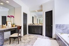 Fantastic bathroom features a nook filled with black make up vanity topped with black marble under ...