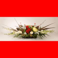JOY TO THE WORLD:  The colors of the holiday season abound in this beautiful arrangement. Contains roses, dendrobium orchids, holiday greenery, berries, feathers, and so much more.  This is a larger oblong piece that can go anywhere in the home. Whether it's for your eyes only, a gift to give, or decor for a gathering; this will certainly put you in the holiday mood!  #MatlackFlorist