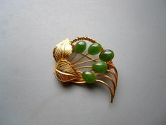 Very intricately designed and made vintage brooch. It is unsigned.    Measures 2 and 1/4 x 1 and 1/2. Goldtone metal forged into beautiful leaves and laurel. Green jade like stones. Leverback type closure. Just gorgeous and rare.    Excellent condition.