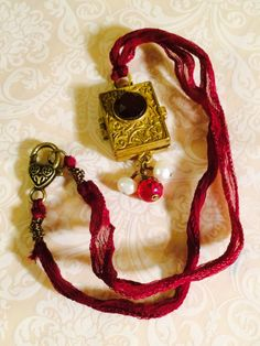 Cupid Awaits locket necklace. Nunn brand Adorned Life ornate gold locket with Cupid image and key on Merlot fairy silk. Pearls, fancy clasp. by GemJelly on Etsy https://www.etsy.com/listing/219659068/cupid-awaits-locket-necklace-nunn-brand
