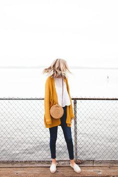 Como usar amarelo em diversos looks: guia completo. Cardigã, blusa branca, calça jeans skinny, bolsa de palha redonda, alpargata branca