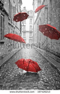 Red umbrellas flying on the street. Conceptual, surreal image. - stock photo