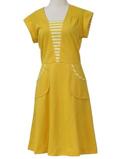 70s -Happenings- Womens mustard and white polyester cap sleeve mid length knit dress. Striped details on the pockets and V-inset below the neckline, a flared skirt with fitted waist, a ruched yoke and back zip closure. There is a teeny black speck below the left pocket, May lessen with further laundering.