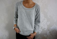 grey sweater with black pants and silver jewelery