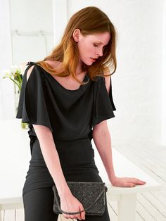 This tunic has lots of unique details that take a simple top to the next level. The sleeves are tied at the shoulders and then fall loosely while the neck drapes forming a cowl effect. It's a long top that should be worn with pants or tucked into a skirt.