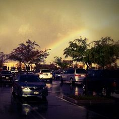 A rainbow in the parking lot after a rainy day.