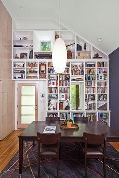 Built in bookshelves on a sloped ceiling wall.