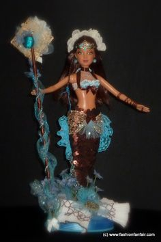 OOAK Mermaid Barbie                   Featuring:      Full facial repaint sealed and finished     Beautiful Restyled Hair     Custom jewelry and crown     Intricate mermaid style costume design     Matching custom made Staff                 All our dolls are one of a kind, designed and drafted on the dolls, so each are very unique works of Art!!      All collectors will enjoy the unique detail we put in our dolls.        Our pictures do not do justice to the real beau