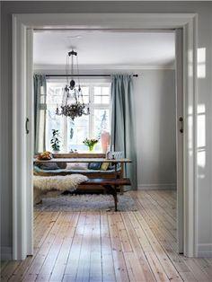 En diskret fargeskala gir et dempet inntrykk. Gardinene er i en kjølig farge, men luner likevel rommet.
