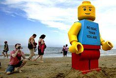 """Un omino lego gigante è """"misteriosamente"""" approdato sulla spiaggia della località olandese di Zandvoort. Il modello, alto 2,5 m, riportava sul torace la scritta 'No real than you are'. La frase non ha molto senso grammaticalmente parlando, a meno che non vi si aggiunga la parola MORE, così da ottenere """"No MORE real than you are"""" (non più reale di quanto lo sia tu). Un mistero alla guerrilla!"""