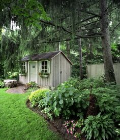 This beautiful yard has fresh and bright green grass, and beautiful flowers and brush surrounding the base of massive trees. #backyardshed