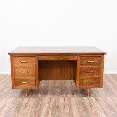 This mid century modern tanker desk is featured in a solid wood with a gorgeous teak finish and shiny brass accents. This large desk is in great condition with 6 large drawers and 2 pull out writing shelves. Retro and regal storage desk! #midcenturymodern #desks #tankerdesk #sandiegovintage #vintagefurniture
