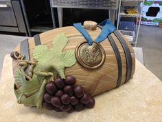Cake in Shape of Half of Wine Barrel Topped with Blue Ribbon and Grapes