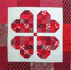 Pieced hearts with half square triangles to make a Valentine's Day four heart table topper. Table Topper Patterns, Quilted Table Toppers, Quilted Table Runners, Heart Quilt Pattern, Quilt Block Patterns, Pattern Blocks, Quilt Blocks, Quilting Projects, Quilting Designs