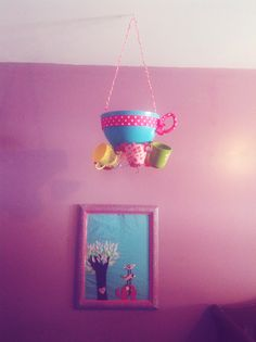 DIY tea party chandelier-plastic salad bowl with ribbon and metal wire for handle- hot glued to a wire picture holder (bent all crazy directions) use picture holder with flat decoration to support tea cups. Paint plastic tea cups and glue onto picture holder. Glue big fake flower to the bottom to cover any excess glue and picture holder base.