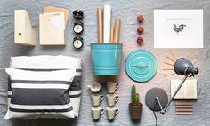 木製のマガジンファイル、ブラックのアラームクロック、ターコイズのスチール容器、ホワイト/グレーの掛け布団カバーセット、ベージュのマグカップ、グレーのワークランプ(すべてイケアの商品)。