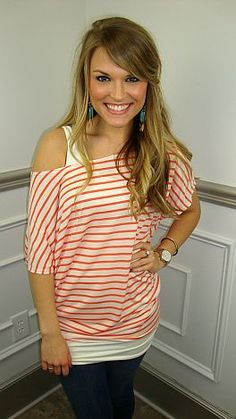 It's like wearing a T-shirt, but CUTER! This soft, knit top is cream with coral stripes. Give it a little spunk by kicking it off one shoulder and layering it over a long, ivory tank, as shown in our photo :)
