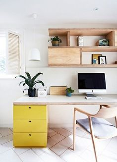 Modern office with natural wood furniture, yellow drawers, and Mac desktop computer.