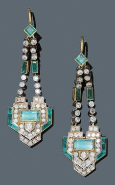 A PAIR OF ART DECO EMERALD AND DIAMOND EAR PENDANTS, CIRCA 1935. Each suspending a geometrical motif set centring a rectangular emerald and set throughout with single-cut diamonds and baguette emeralds, from two chains set with diamonds, two baguette emeralds, and a square-cut emerald, mounted in silver and gold. Length 6.3 cm. #ArtDeco #earrings
