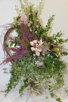 English garden style arrangement includes ivy, coleus, heather, grapevine, spray roses, snapdragons and larkspur arranged in an urn. frugalflower.com Ivy Flower, Flower Spray, Spray Roses, Flowers, Large Floral Arrangements, Spring Wreaths, Garden Styles, Urn, Grape Vines