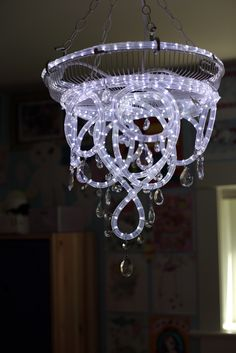 Rope light chandelier. It looks to be made from a fan cover, rope lighting and glass pendants - genius!