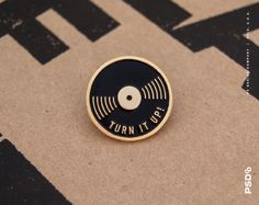 Turn It Up! - Vinyl Enamel Pin  1 Die-stamped Pin available in Gold or Silver Metal with Enamel Fill & Rubber Clasp. Includes a backer card and is shipped in a bubble mailer.  ——  © PS Design Co. / Columbus, Ohio U.S.A.