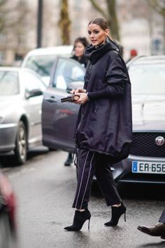 Olivia Palermo wears a black Valentino 'VLTN' long bomber coat with a hoodie outside Valentino during Paris Fashion Week Womenswear Fall/Winter...