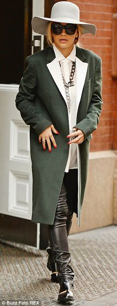 Green coat with white lapels + grey hat + white shirt + multiple silver necklaces + brown boots