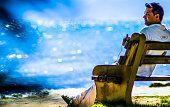 Homem sozinho sentado no banco observa o mar na praia do Perequê em Ilhabela, Brasil.