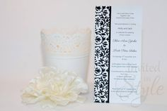 Handmade wedding invitation - White metallic DL size card decorated with designer metallic paper in Verona Black and thin black sating ribbon for that flawless finish.