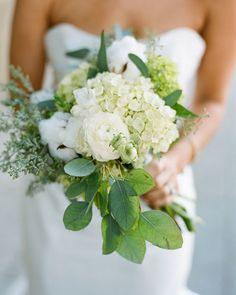 Lauren's bouquet, wrapped in a simple white mohair band, consisted of seeded eucalyptus, cotton balls on the stalk, ranunculus, hydrangea, anemones, dahlias, and freesia. She wanted all of the floral arrangements to be textural, casual, warm, lush, and seasonal.