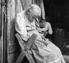 Alte Frau sitzt zusammengesunken auf einem Holzstuhl an einer Holzwand und schläft ullstein bild - ullstein bild/Timeline Images #30er #30s #daydreams #entspannen #relax #enjoy #sleep #schlafen #tagträumen #Tagträumer #träumen #Sonne #Sommer #Nickerchen #nap #Frau #alt #Menschen #Stuhl