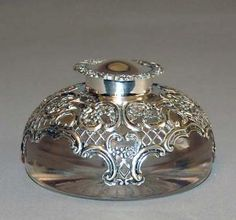 Elegant sterling silver repousse and reticulated cut crystal inkwell- artistry as you will ever likely find. Inkwell attributed to the maker William Comyns, London, 1898. Sterling silver mount scallops and flowers motif, lid also having a pierced design and scalloped edging. The crystal base has a deeply cut starburst pattern that is reflected through the crystal, the combination making for an overall fantastic and sparkling display.
