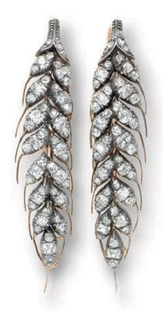 A PAIR OF ANTIQUE DIAMOND EAR PENDANTS. Each elongated hoop designed as a leaf set with old mine and rose-cut diamonds, mounted in silver-topped gold, circa 1840, with pendant hoops for suspension