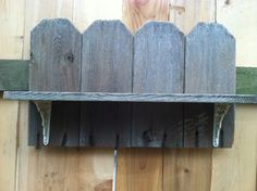Shelf made from old fence boards and old, painted wrought iron shelf brackets purchased at a garage sale.  Made by son, Web.  There are a few other views of same shelf on this board.