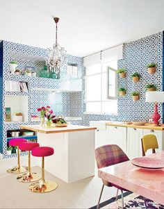 Feminine kitchen with bright blue wallpaper, reclaimed wood countertops, and a chandelier