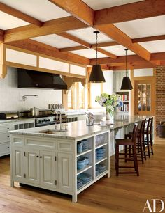 Crisscrossing ceiling beams and wide-plank floors lend an Arts and Crafts feel to the kitchen; the sink fittings are by Kohler, the hood and range are by Viking, and the barstools are by Ann-Morris Antiques.