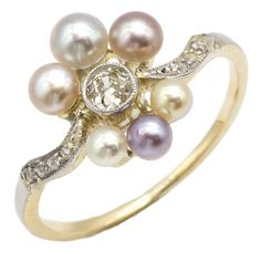 Cream Puff: Sweets for the sweet! A perfectly divine Art Nouveau ring with luscious organic details. This scrumptious collection of creamy cultured pearls in different shades of pastel create a soft pillow around a single cushiony old mine cut diamond. Light and airy on the hand with a delicate sprinkling of sugary rose cut diamonds on the shoulders to sweeten the deal. Made from 18k yellow gold with a thin layer of platinum along the top. Maloys.com